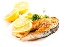 Grilled salmon and vegetables on plate with lemons Royalty Free Stock Photography