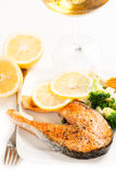 Grilled salmon and vegetables on plate with wine Stock Photography