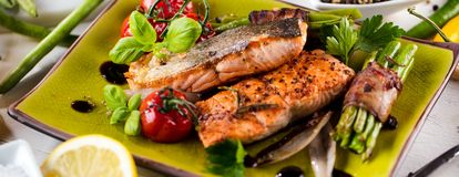 Grilled salmon with vegetables served on green stone plate on wooden table. stock photography