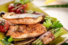 Grilled salmon with vegetables served on green stone plate on wooden table. royalty free stock photo
