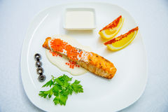 Grilled salmon and vegetables. On a white plate Grilled salmon and vegetables Stock Images