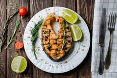 Grilled salmon on white plate. On wooden background Royalty Free Stock Photos