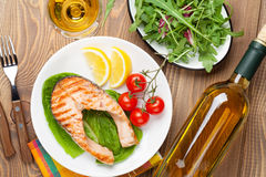 Grilled salmon and whtie wine on wooden table Royalty Free Stock Images