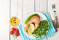Grilled salmon and whtie wine on wooden table Stock Images