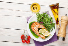 Grilled salmon and whtie wine on wooden table Royalty Free Stock Photos