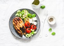 Grilled salmon, zucchini, baked cherry tomatoes and feta cheese - healthy balanced meal on light background
