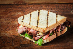 Grilled sandwich with beef and herbs. Grilled sandwich from a BBQ with rare roast beef and fresh leafy green herbs on a rustic wooden table royalty free stock photography