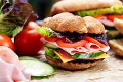 Grilled Sandwich with lettuce, slices of fresh tomatoes, cucumber, red onion, salami, ham and cheese. Stock Photography
