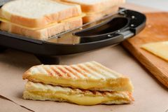 Grilled sandwich with oozing cheese. Grilled sandwich triangles with oozing melted cheese. Cooking with a panini press. Tasty food recipe royalty free stock photography