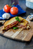 Grilled sandwich with some basil and tomatoes. In the background Royalty Free Stock Photo