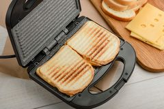 Grilled sandwiches in panini press. And their ingredients on cutting board. Making snacks for lunch royalty free stock photos