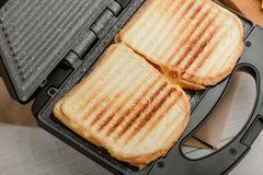 Grilled sandwiches in panini press. Grilled sandwiches in a panini press. Useful kitchen tool for beautiful and ruddy crust royalty free stock photography