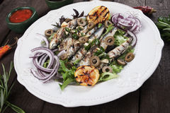 Grilled sardine fish with lettuce and olives Royalty Free Stock Photo
