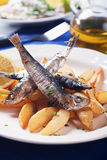 Grilled sardine fish with potato wedges Stock Photos
