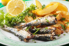 Grilled sardine fish with potato wedges Stock Images