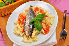 Grilled sardine on some tomato pasta. Grilled organic sardine on some tomato pasta Stock Photo
