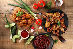 Grilled sausage, chicken leg and wings with vegetables Royalty Free Stock Image