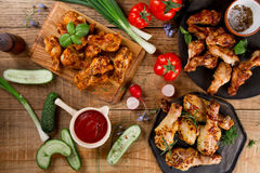 Grilled sausage, chicken leg and wings with vegetables Royalty Free Stock Images