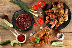 Grilled sausage, chicken leg and wings with vegetables Stock Photos