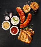 Grilled sausage with different kinds of dips on a black background Stock Photos