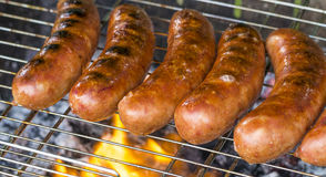 Grilled sausage on the flaming grill Royalty Free Stock Photo