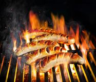 Grilled sausage on the flaming grill. With smoke royalty free stock photo