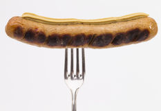 Grilled sausage with fork Royalty Free Stock Images