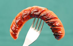 Grilled sausage on a fork. Royalty Free Stock Images