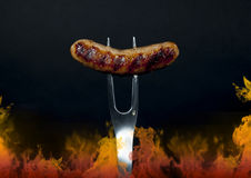 Grilled Sausage on Fork with Flames. A grilled Italian sausage on a stainless steel barbecue fork with drop of fat running down fork and flames along lower and stock image