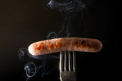 Grilled sausage on a fork fuming smoke black background Royalty Free Stock Image