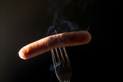 Grilled sausage on a fork fuming smoke black background Royalty Free Stock Images