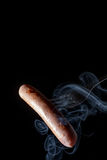 Grilled sausage on a fork fuming smoke black background Stock Photo