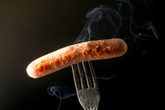 Grilled sausage on a fork fuming smoke black background Royalty Free Stock Photography
