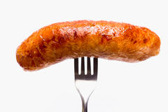 Grilled Sausage. On a fork on white background Stock Photography