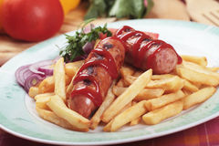 Grilled sausage with french fries Royalty Free Stock Images