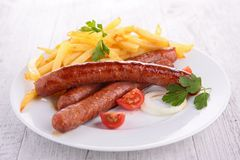 Grilled sausage and french fries Stock Images