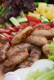 Grilled sausage, fresh herbs, tomatoes, onions. Clolose-up. selective focus on the center of the frame Stock Images