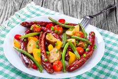 Grilled sausage with garlic, potato, cherry tomatoes, green beans, top-view Royalty Free Stock Photography