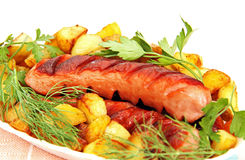 Grilled sausage with garnish on the plate. Stock Image