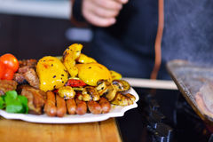 Grilled sausage with grilled vegetables on kitchen table Royalty Free Stock Image