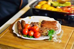 Grilled sausage with grilled vegetables on kitchen table Royalty Free Stock Photos