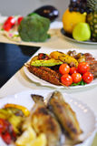 Grilled sausage with grilled vegetables on kitchen table Stock Photos