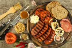 Grilled sausage with mustard on a wooden cutting board. Summer barbecue party. Fat meal. Stock Image