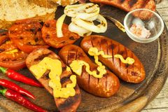 Grilled sausage with mustard on a wooden cutting board. Summer barbecue party. Fat meal. Stock Photo