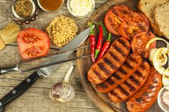 Grilled sausage with mustard on a wooden cutting board. Summer barbecue party. Fat meal. Royalty Free Stock Photos