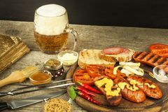 Grilled sausage with mustard on a wooden cutting board. Summer barbecue party. Fat meal. Royalty Free Stock Image
