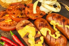 Grilled sausage with mustard on a wooden cutting board. Summer barbecue party. Fat meal. Royalty Free Stock Photo