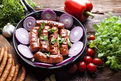 Grilled sausage with onion in a pan, raw meat and vegetables Royalty Free Stock Photo