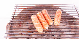 Grilled sausage over a hot barbecue grill Royalty Free Stock Photos
