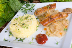 Grilled sausage with pickled cabbage and mashed potatoes Royalty Free Stock Images